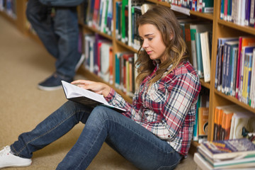Happy student reading book on library floor