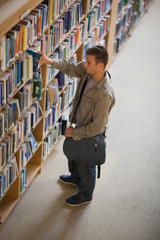 Student taking a book from shelf in library