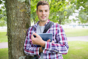 Smiling student leaning on tree holding his digital tablet