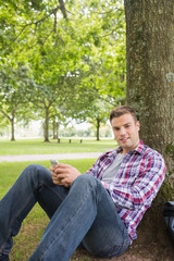 Happy student sending a text outside leaning on tree