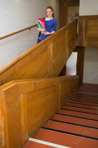 Happy student holding folders on the stairs looking at camera