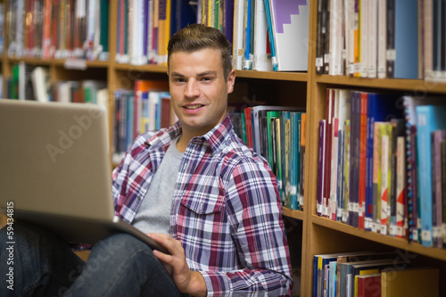 Smiling young student sitting on library floor using laptop