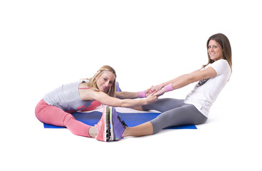 Two young women doing yoga stretching exercises