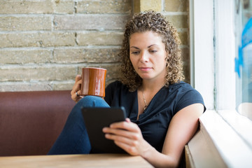 Woman Using Digital Tablet While Having Coffee In Cafe