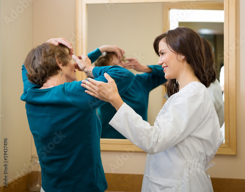 Ophthalmologist Assisting Woman To Insert Contact Lens