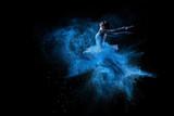 Fototapety Young beautiful dancer jumping into blue powder cloud