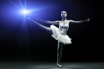 Ballet dancer in white tutu posing on one leg