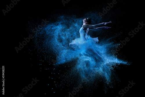 Canvas Dans Young beautiful dancer jumping into blue powder cloud