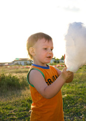 Adorable little boy enjoying cotton candy