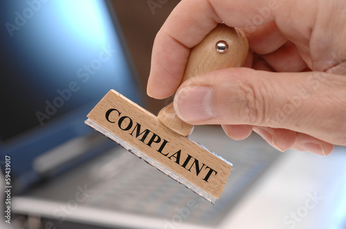 complaint marked on rubber stamp in hand