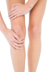 Close-up mid section of a young woman with knee pain