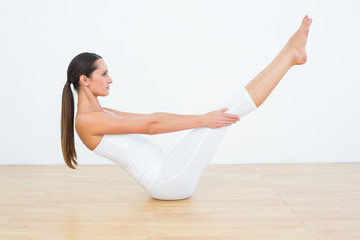 Toned woman doing the boat pose in fitness studio