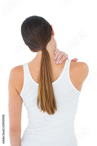 Rear view of a casual woman suffering from neck ache