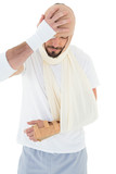 Man with head tied up in bandage and broken hand