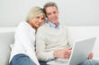 Happy casual couple using laptop at home