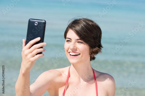 lachende frau fotografiert sich am meer
