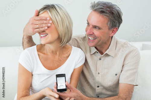 Man covering woman's eyes to offer her an engagement ring