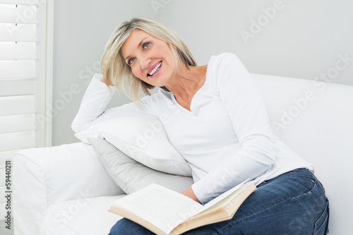 Happy woman with a book at home