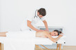 Male physiotherapist massaging woman's back