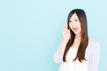 young asian woman calling on blue background