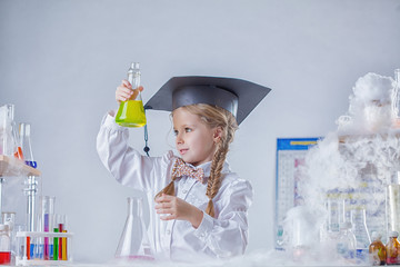 Portrait of inquisitive girl looking at test tube