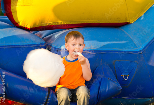 Cute small boy enjoying a stick of candy floss