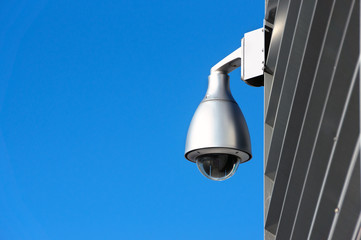 security camera on wall against blue sky