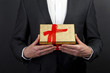 close up of man hands holding gift box over dark background