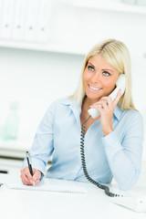frau schreibt beim telefongespräch