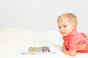 little boy playing checkers, early education
