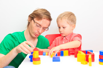 Father and son playing with colorful blocks