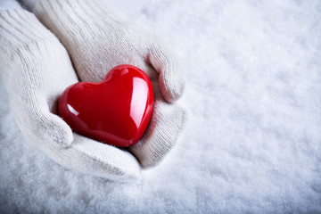 Female hands in white knitted mittens with a glossy red heart on