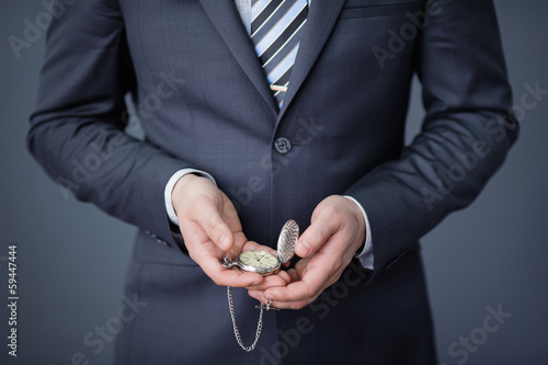 close-up of a businessman displaying an open pocket-watch in his