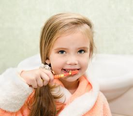 Smiling little girl brushing teeth