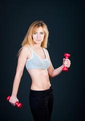 Young beautiful woman lifting dumbbells