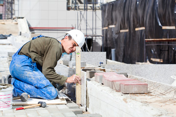 Worker with level examining marble tiles installation
