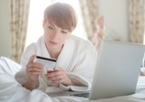 Woman in a bathrobe paying online with a credit card