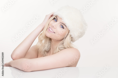 Beautiful naked blond girl in a white winter hat