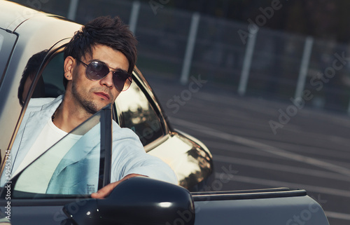 Handsome young man sit in his car.