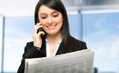 Businesswoman talking on the phone while reading the newspaper