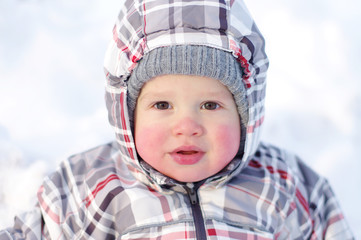 baby with rosy cheeks in winter outdoors
