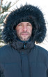 Portrait of confident man wearing fur hooded parka coat at the s
