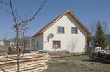 New house in countryside in springtime and woodpiles. poster