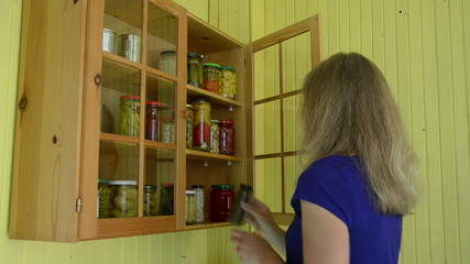 Girl open food rack put few jars with canned organic products