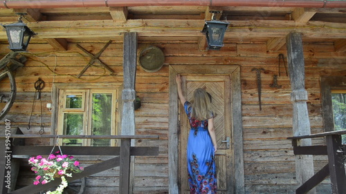 woman looking key over old house wooden door frame