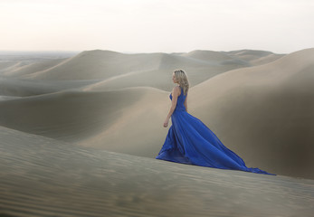 Woman in blue long dress on a dune of the desert