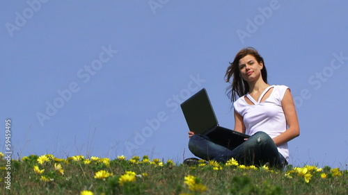 Teenage girl with a laptop in a blooming field