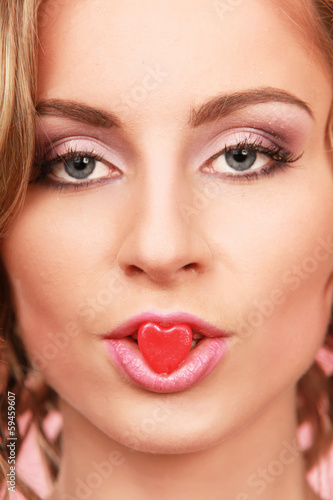 face of beautiful girl smiling and holding a little heart