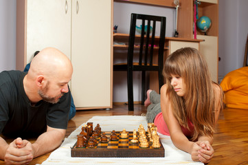Father and faughter playing chess