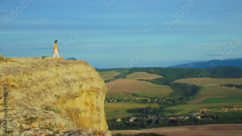 Man standing on a high peak and admiring the view